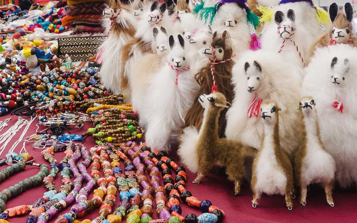 Fluffy llama dolls next to colorful bracelets and necklaces at a Peruvian souvenir market.