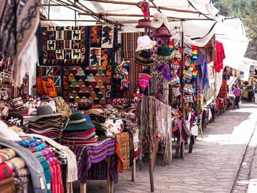 An outdoor Peruvian market. Stalls are selling alpaca scarves, hats, pompoms, and wall hangings.