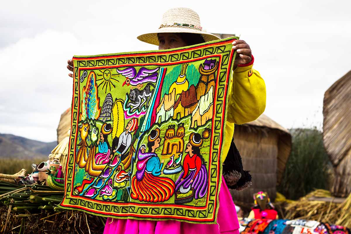 An Andean woman holds up a woven textile piece that shows scenes of Andean life.
