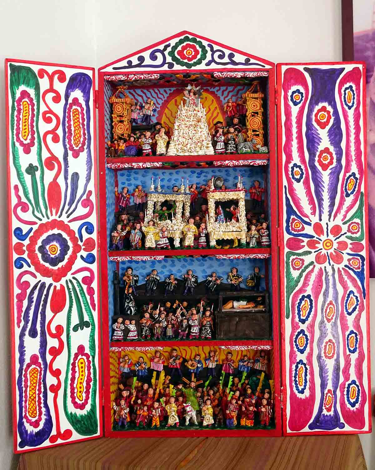 An altar-like retablo with colorful hand-painted designs on the doors and hand-carved figures inside