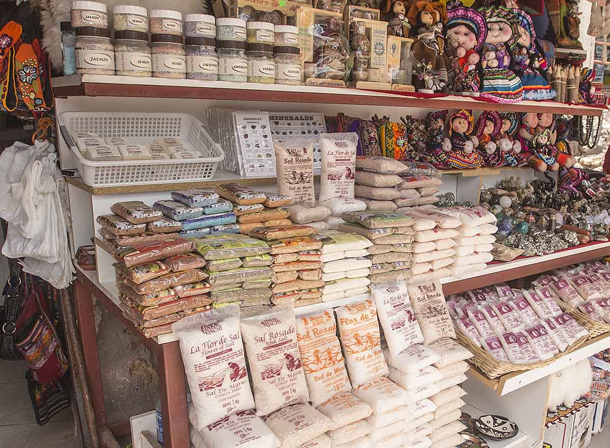 A shop with bags of Peruvian salt from Maras, including white and pink salt, mixed herbs and spices.