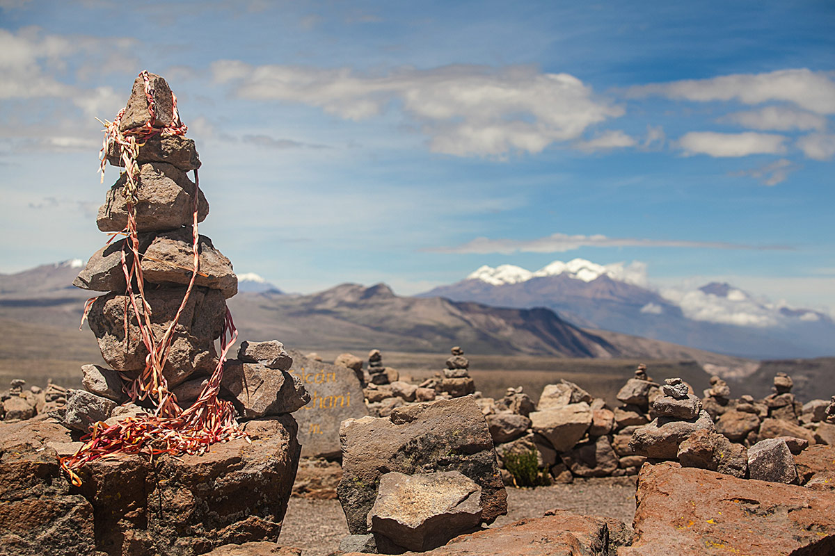 A variety of stacked rocks in the foreground at the Patapampa Pass in the Salinas and Aguada Blanca National Reserve with mountains and snowy peaks far off in the distance.