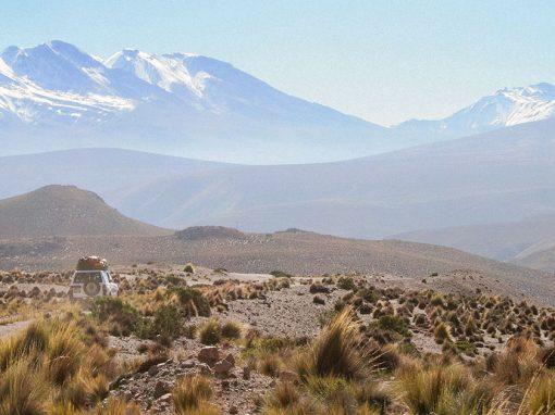 A white car driving along a dirt road through the barren Salinas and Aguada Blanca National Reserve.