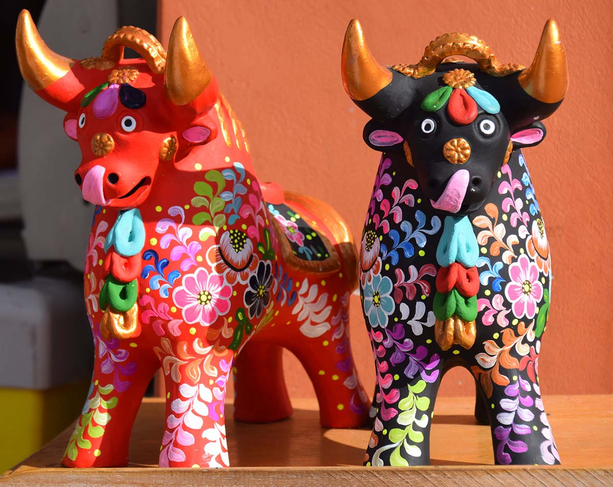 A red ceramic bull and a black one with brightly colored hand-painted flower designs.