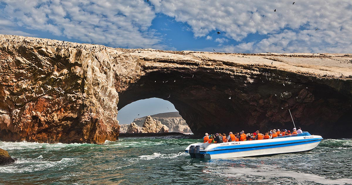 A boat passes by an arch rock formation jutting out of the water on a Ballestas Islands tour.