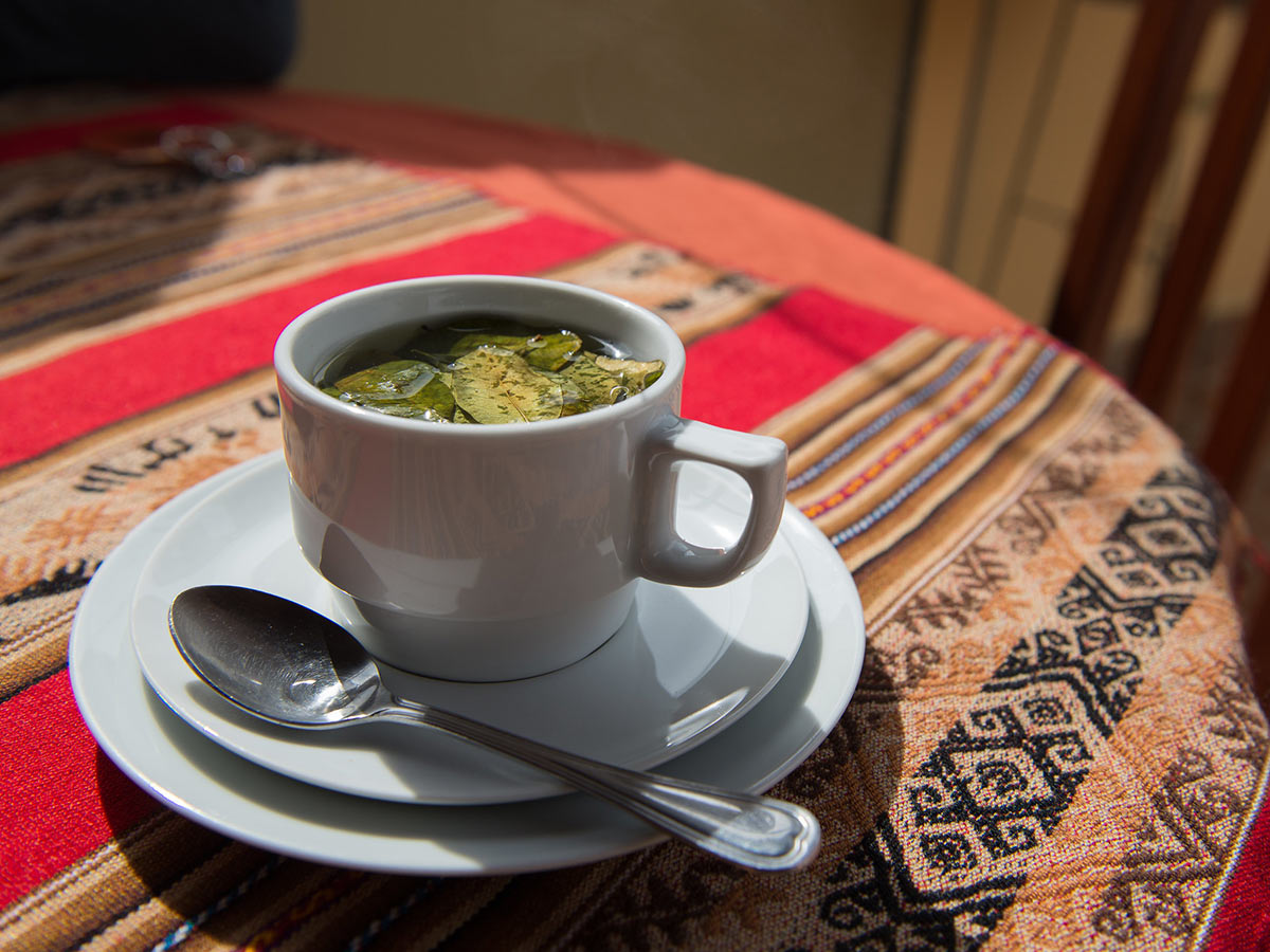 A cup of coca tea on a table covered in a cloth with an Andean design.