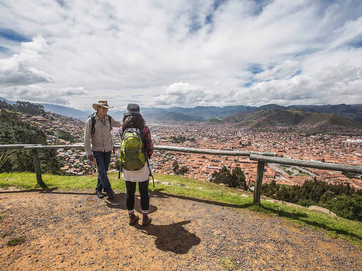 Cusco tour guide talking with a traveler at a lookout point over the city of Cusco.