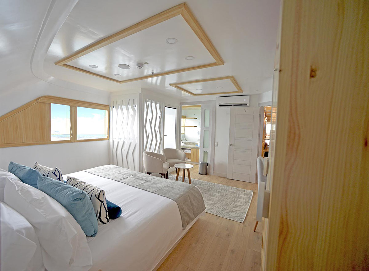 A spacious cabin on the Sea Star Galapagos Cruise, light wood finishes and modern decor furnish the room.