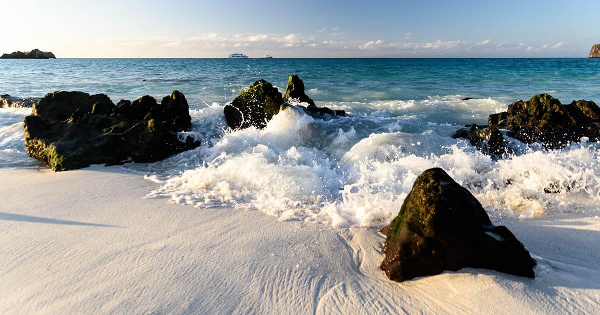 Ocean waves crash onto white sand on one of the galapagos island beaches on Espanola Island.