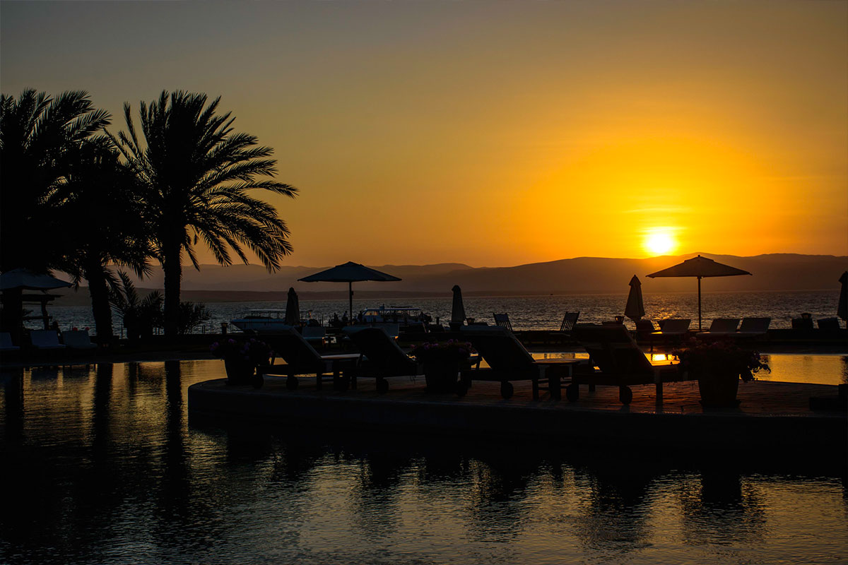 An orange and yellow sunset over the Paracas Peninsula with umbrella and palm tree silhouettes.