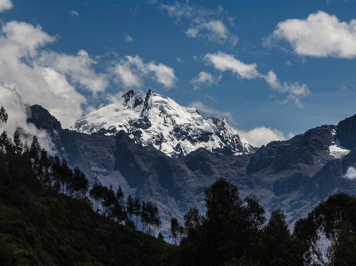 Dramatic snow covered peak covered with some clouds as viewed in the Sacred Valley in Peru.