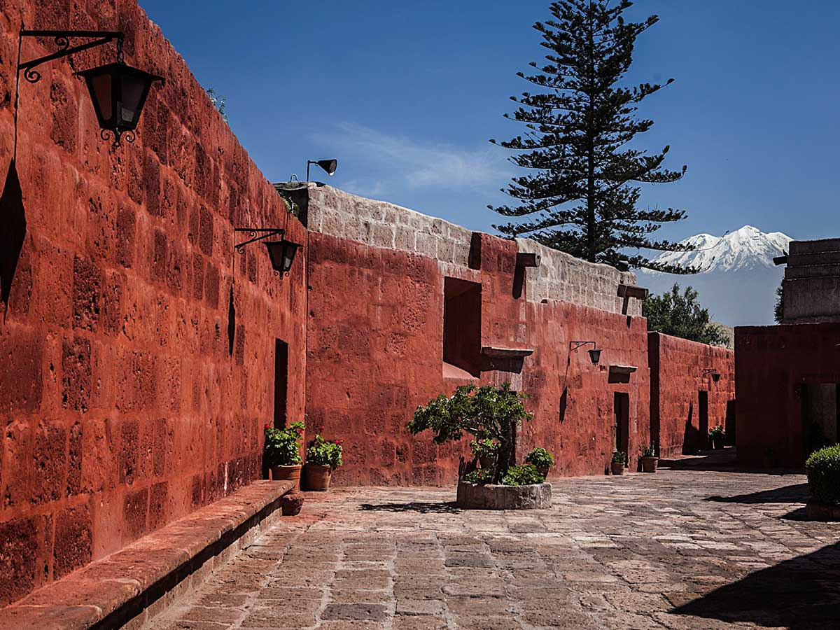 Red walls of the Santa Catalina Monastery with the snow-covered Misti Volcano in the background.