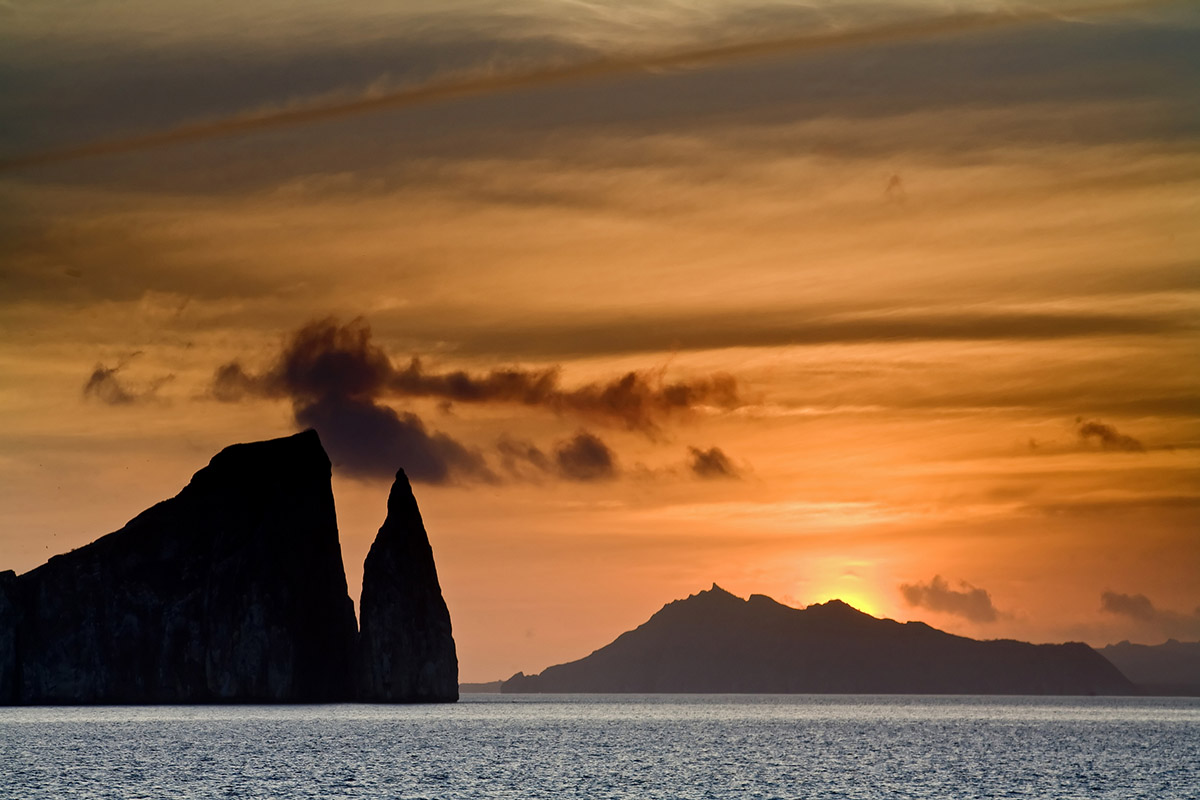 An orange and yellow sunset silhouettes Kicker Rock, a jagged rock formation jutting out of the ocean.