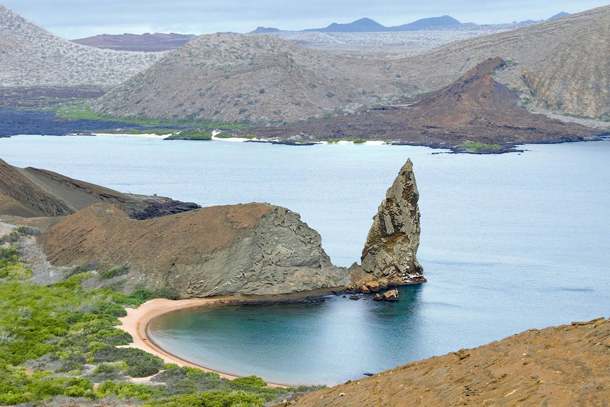 A giant sharp rock juts out from a bay on Bartolome Island. Mountains can be seen in the distance.