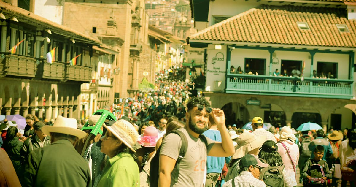 A tourist in Cusco lifting his sunglasses to look at something, amidst a crowd of people.