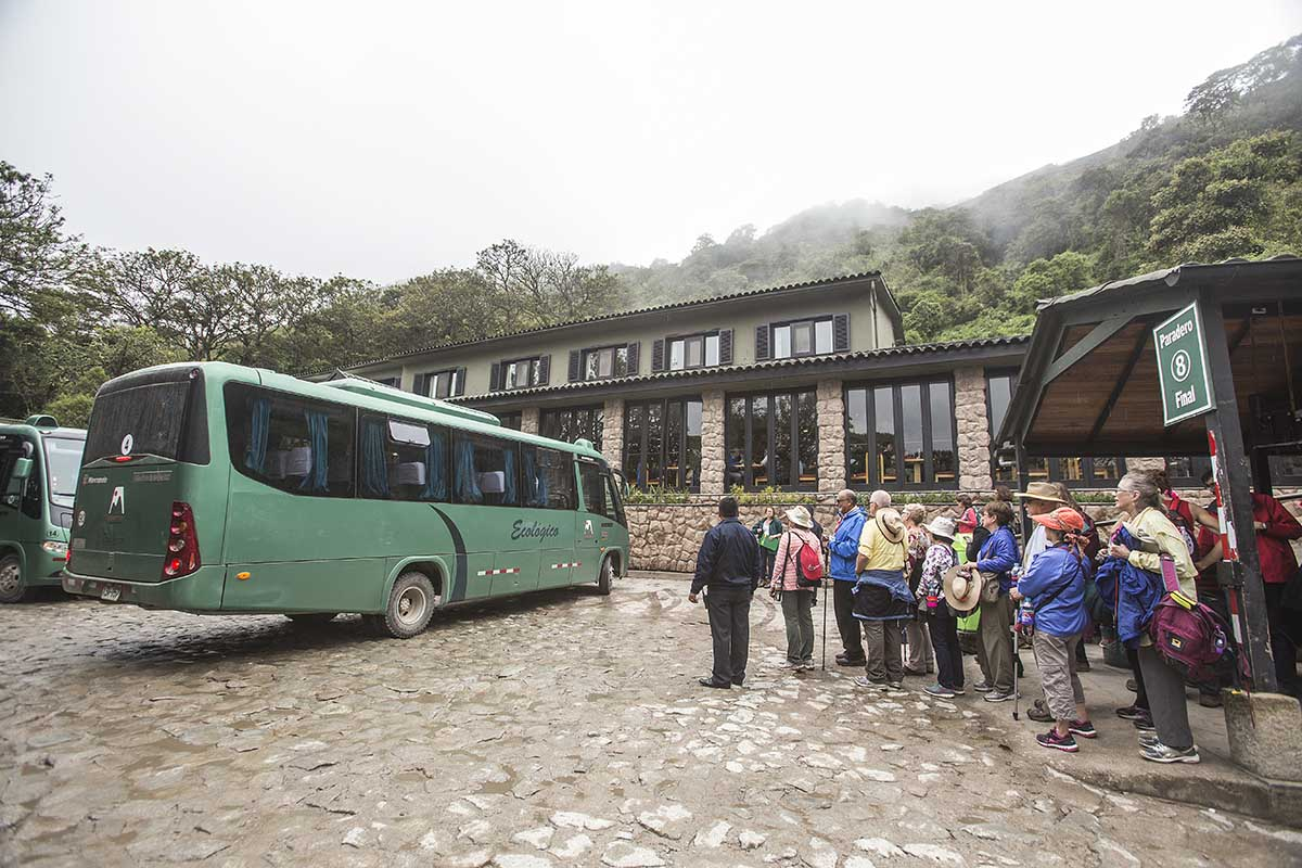 A crowd of Machu Picchu visitors waiting to board the green shuttle bus that returns to Aguas Calientes down the mountain from the ruins.