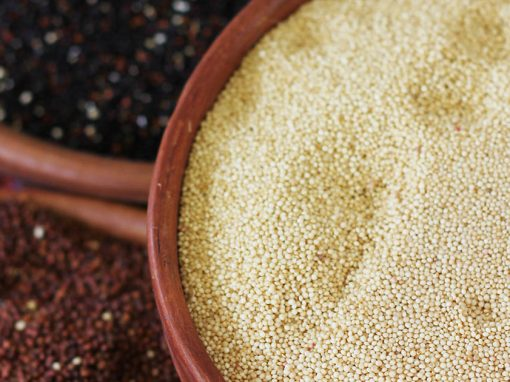 Three bowls of quinoa. One with red seeds, one with black seeds and another one with white seeds.