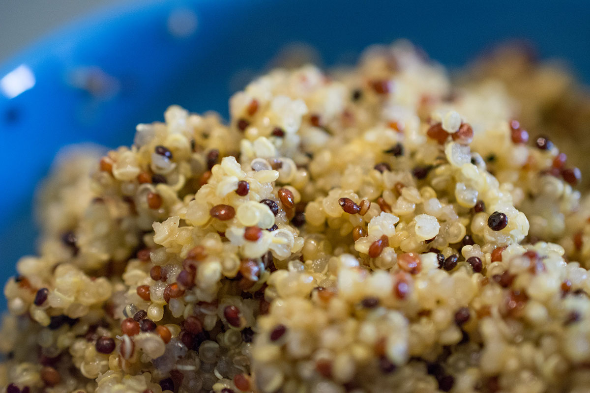 Fluffy cooked white and red quinoa in a blue bowl.
