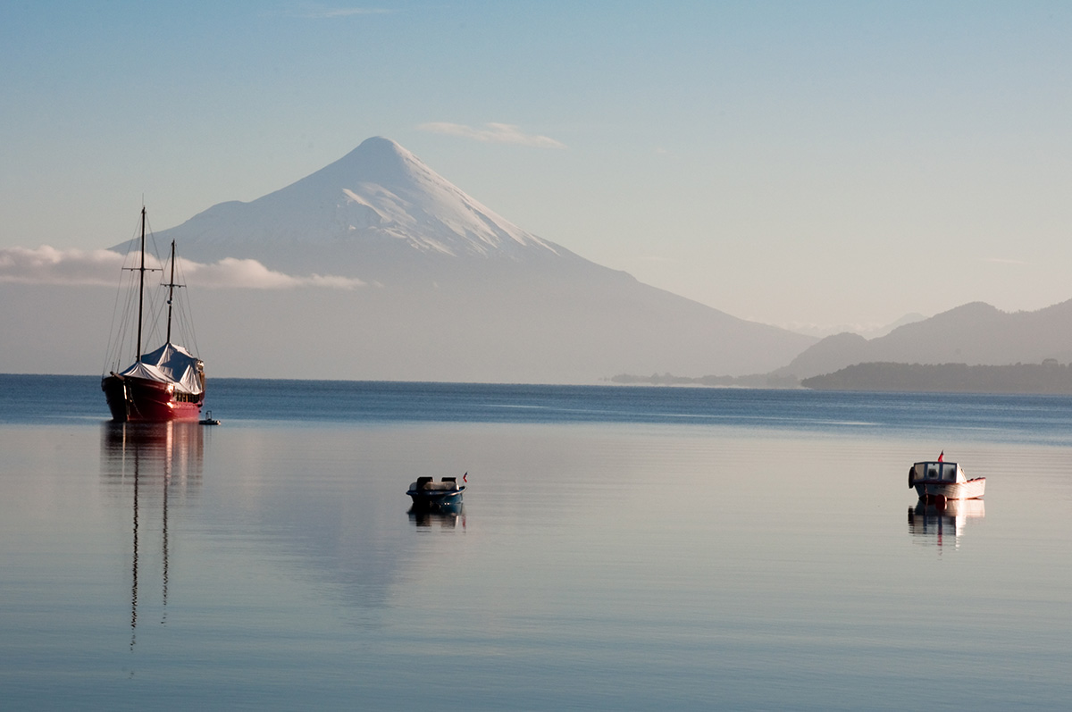 A sailboat and two dinghies sit in a calm harbor with a snowcapped volcano in the distance.