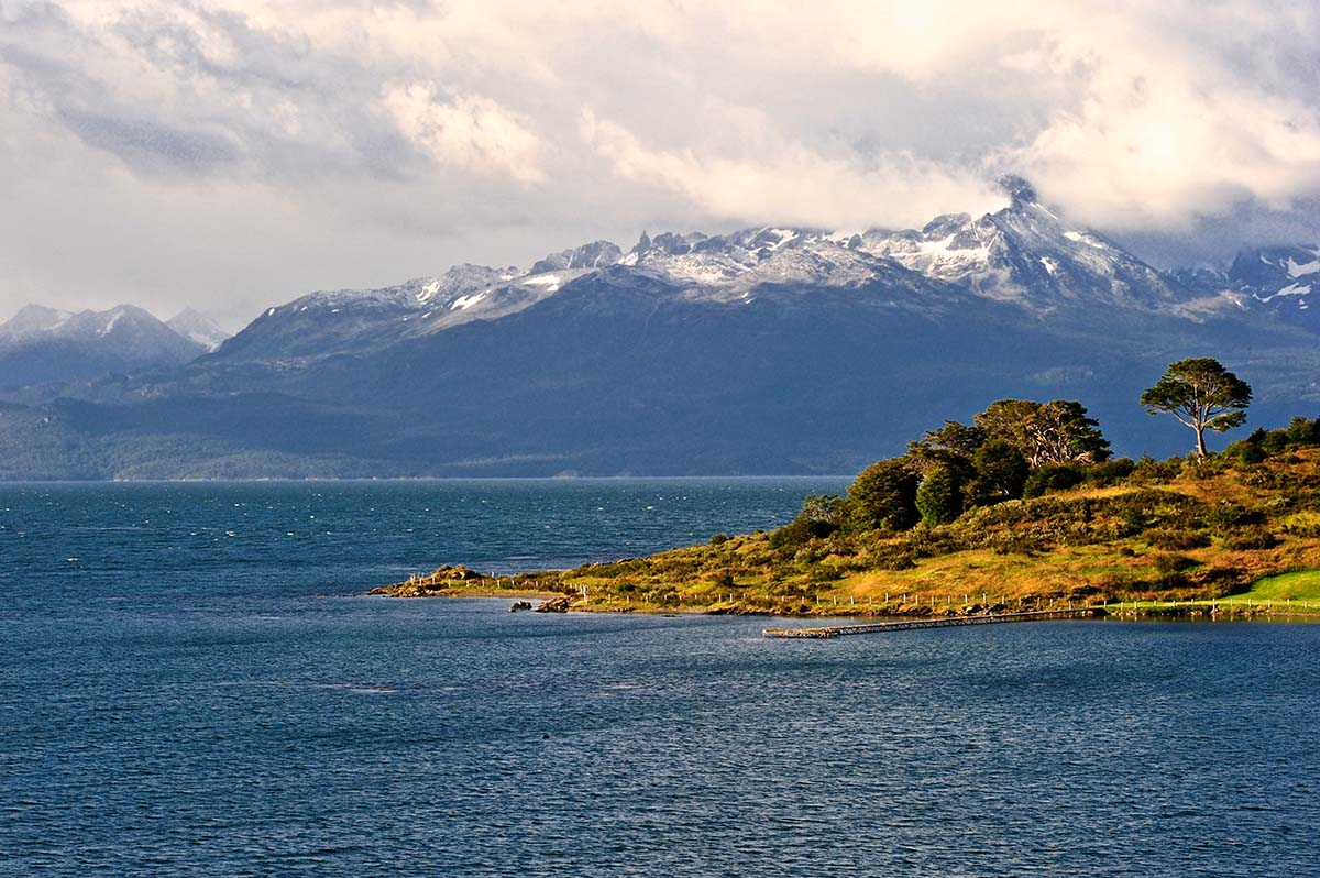 A grassy hills sticks out into the sea with snowcapped mountains in the distance.