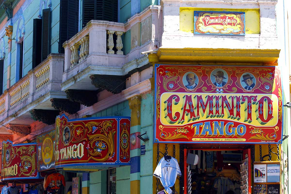 A festive tango scene in Buenos Aires, with red and yellow signs on the shops and entryways.