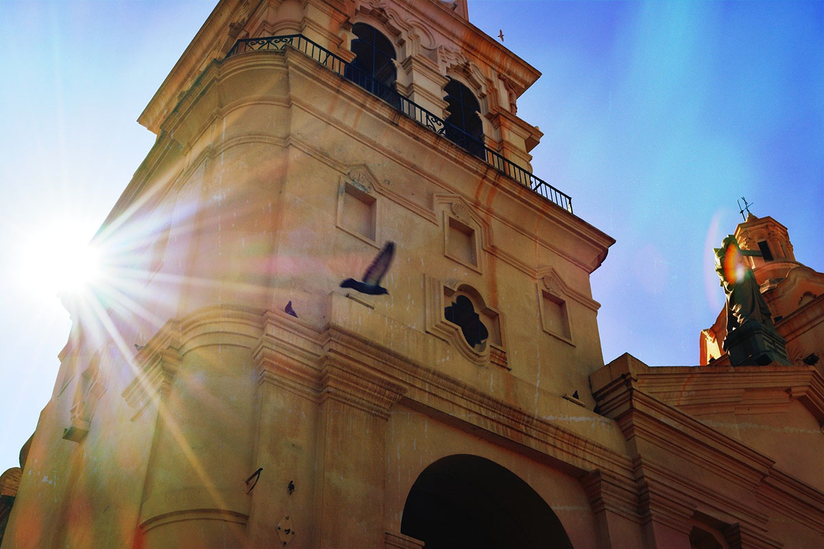 The sun shining on a colonial church in Córdoba, Argentina as a pigeon flies past.