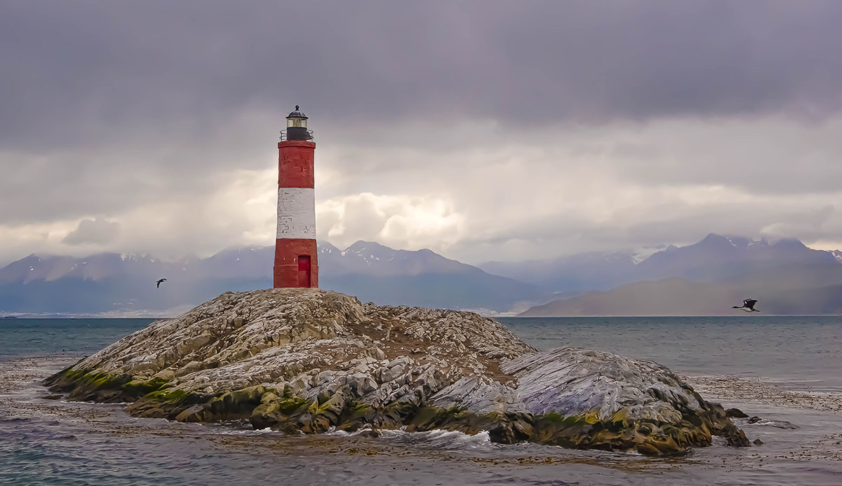 A red and white lighthouse jets out of a rock in the beagle channel on a cloudy day with distant mountains.