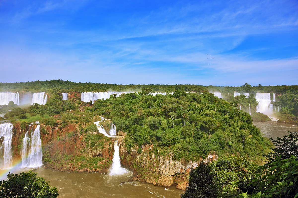 A rainbow forming amidst the numerous waterfalls and jungle landscapes of Iguazu Falls.