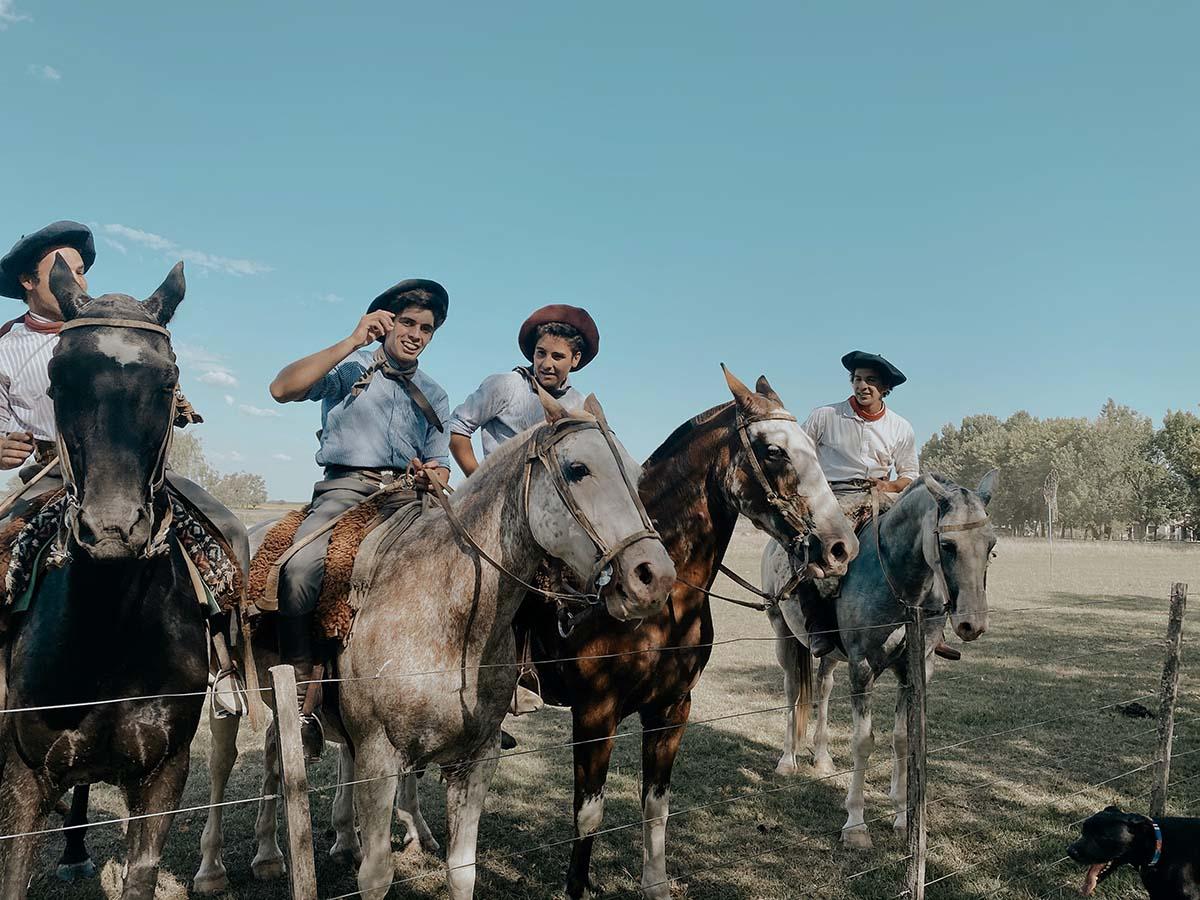 Four men in traditional gaucho, or cowboy, attire ride horses across a field in San Antonio de Areco.