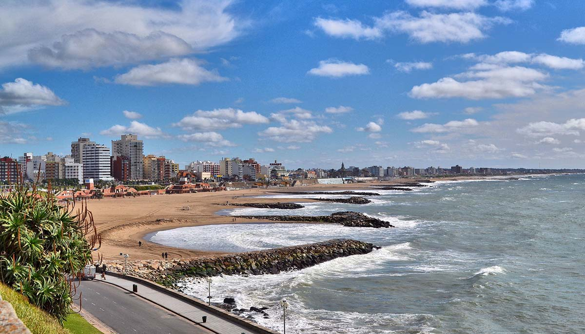 The sandy coast and sea of Mar del Plata on a partly cloudy day, a popular beach town in Argentina.