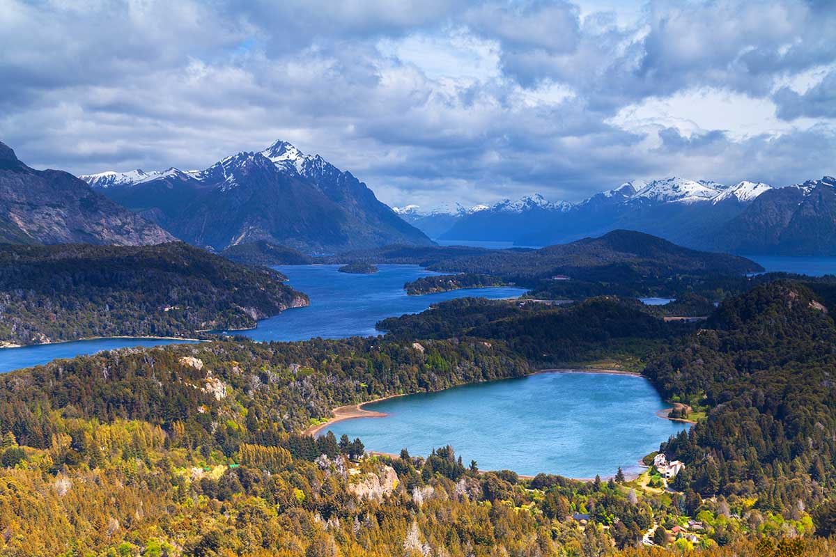 The stunning glacial lakes and snow-capped mountains of Bariloche on a partly cloudy day.