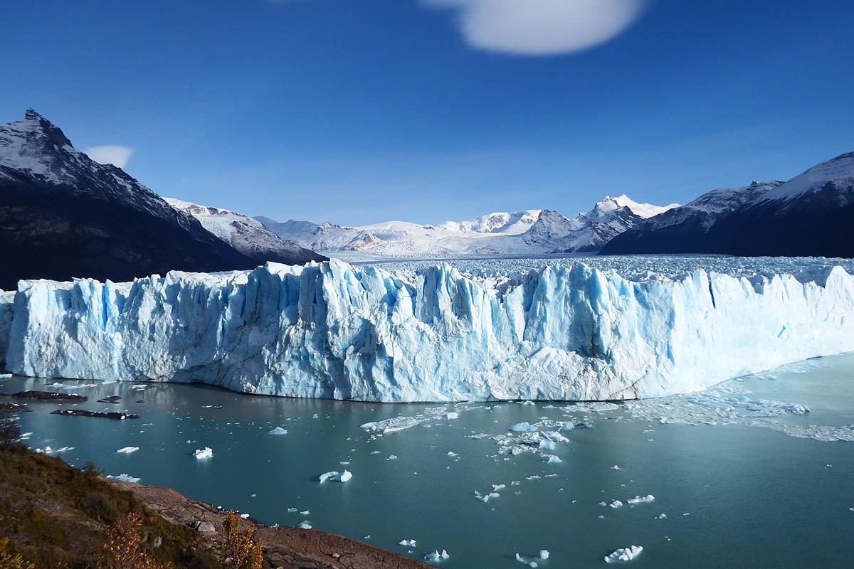 The glacial waters and snowcapped mountains surrounding Perito Moreno Glacier, one of the top places to visit in Argentina's Patagonia region.