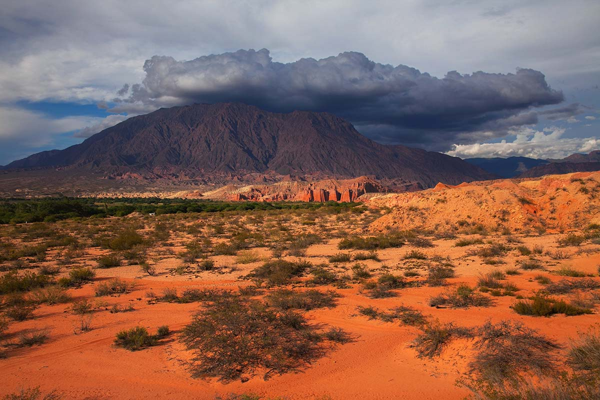Red sand desert and red-colored mountains under a cloudy sky in Salta, Argentina.