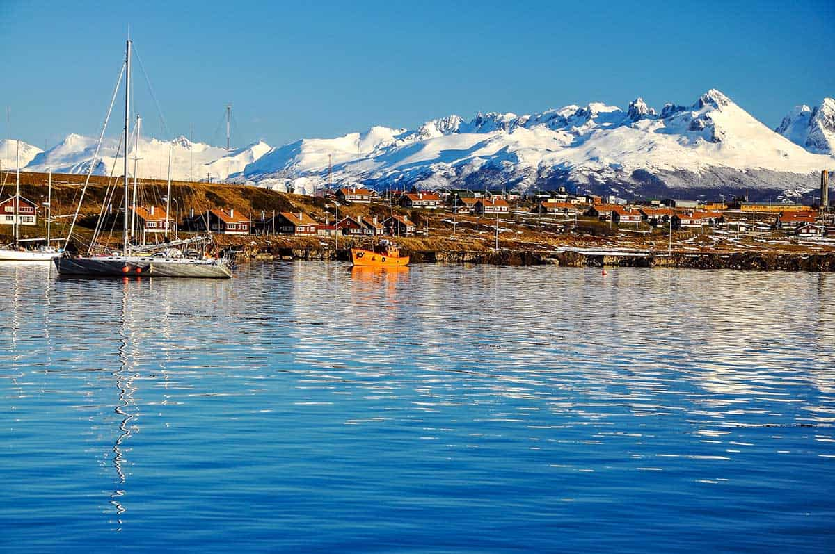 Sailboats in the waters of Ushuaia in Argentinian Patagonia with snowcapped mountains and blue skies.