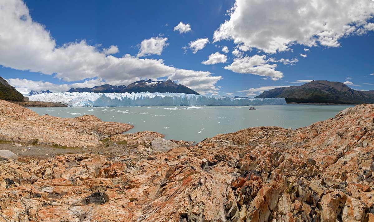 Rocky coast, glacial waters, glaciers, mountains and blue partly cloudy skies at Parque Nacional Los Glaciares.