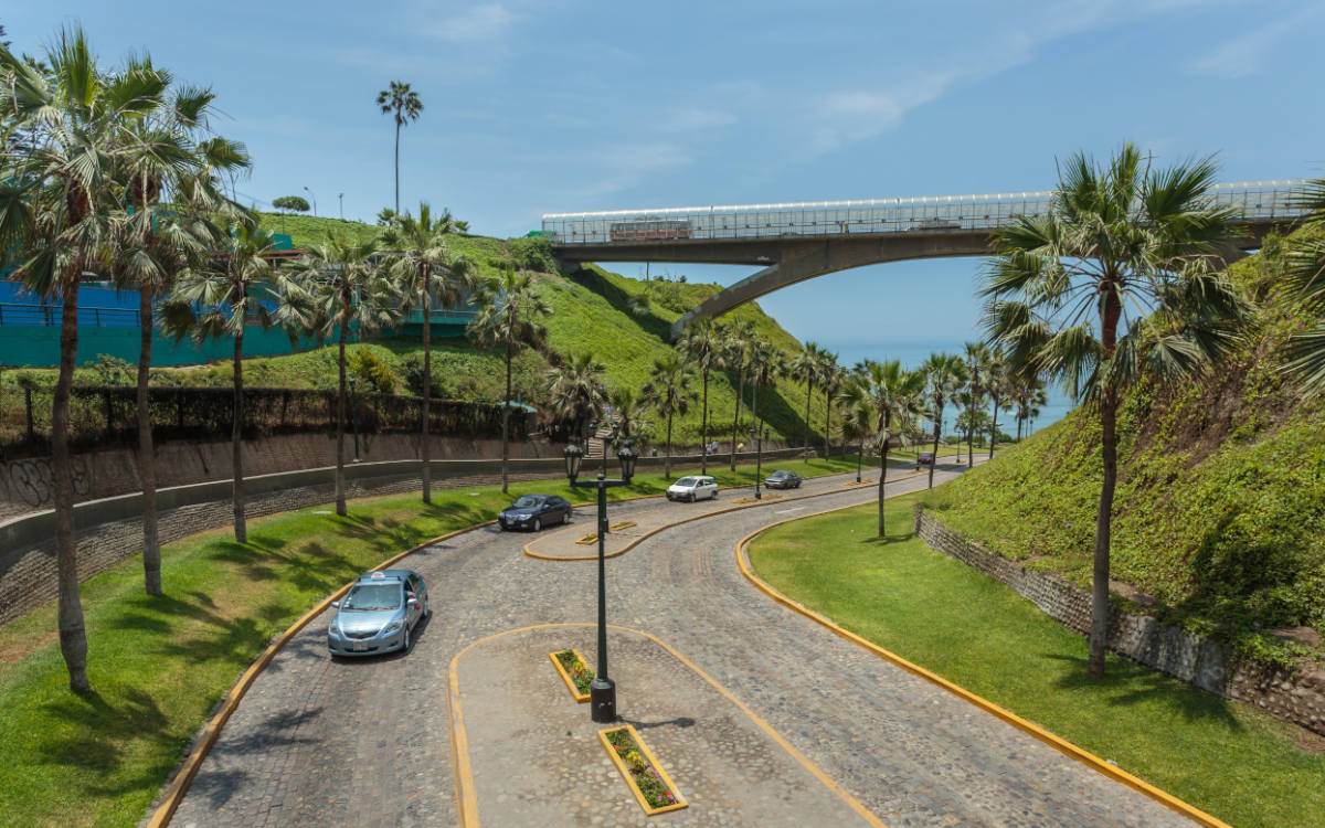 Lightly trafficked cobbled road in Miraflores with trees on the sides leading to the Pacific Ocean.