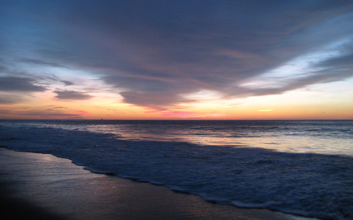 An orange, purple and red sunset over the Pacific Ocean in Mancora, Peru, a popular beach town.