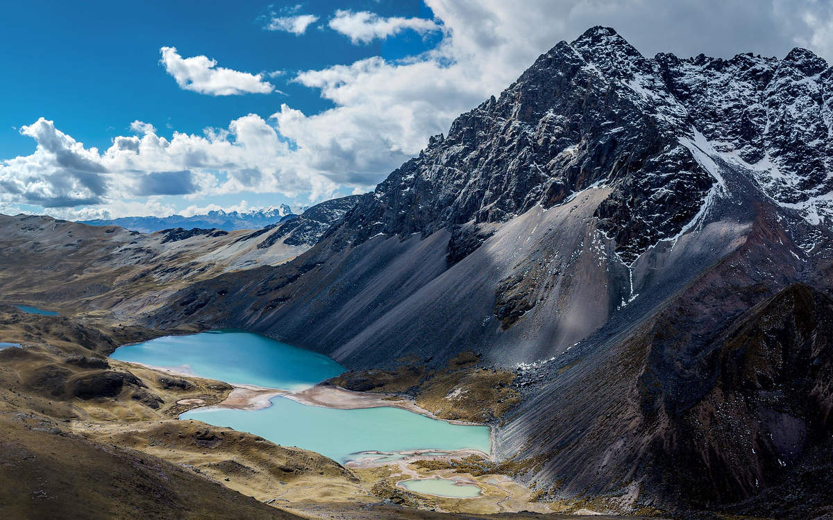 The Andes Mountains on a partly cloudy day with turquoise lakes at the base of a grey peak.