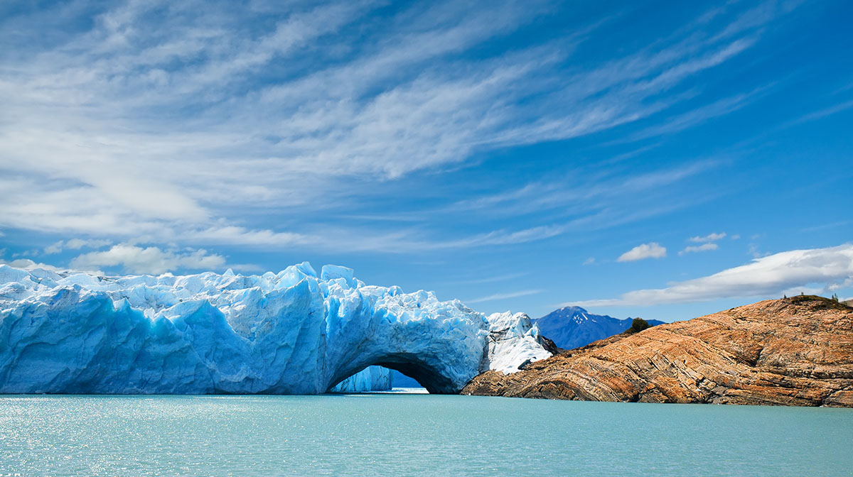"""Icy blue waters surrounding white and blue glaciers under a blue sky at el Calafate, known as """"gateway to the glaciers."""""""