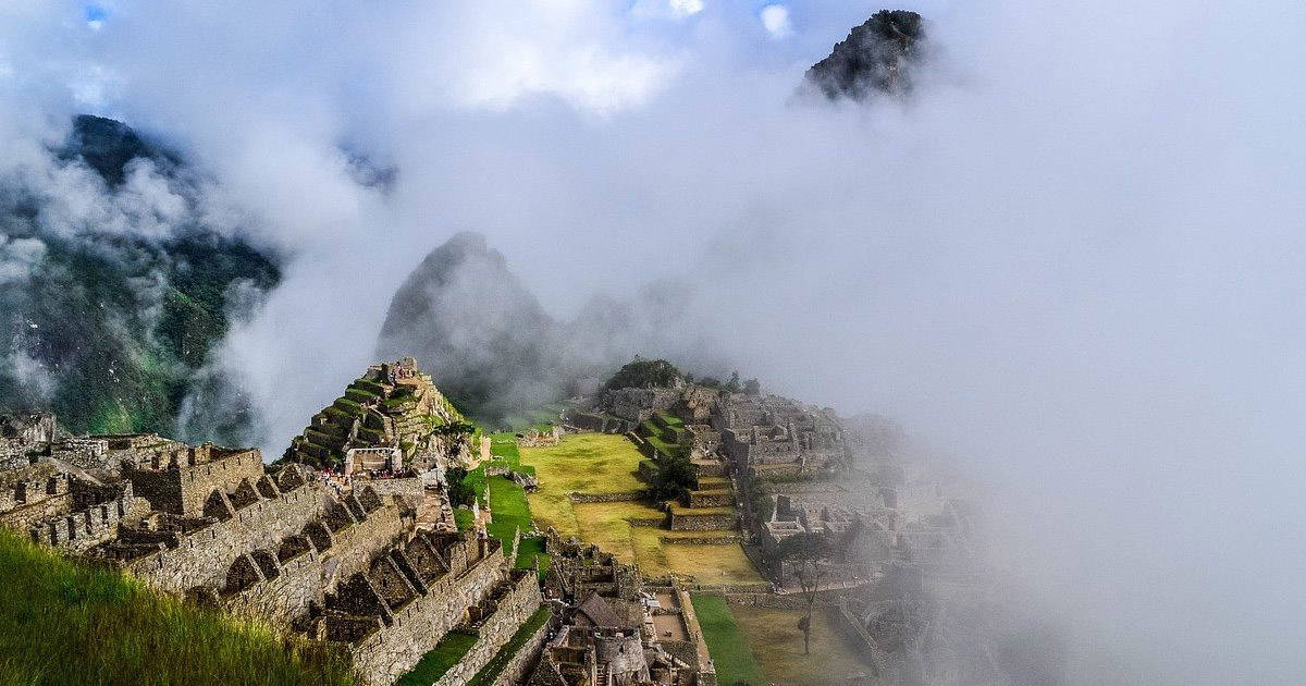 Fog rolling in and covering the mountains behind Machu Picchu and part of the ruins.
