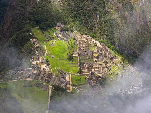 The hilltop Inca city of Machu Picchu surrounded by green mountains and white cloudy mist.