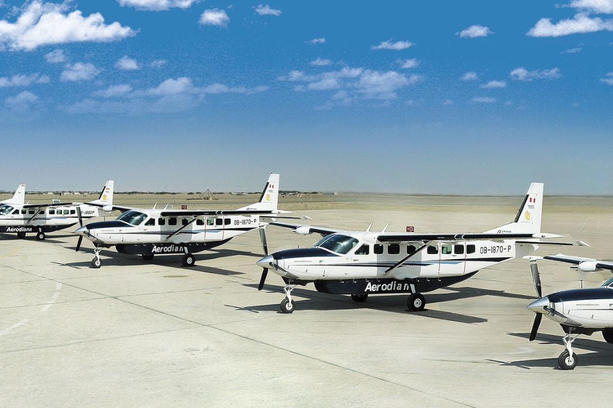 Small white aircraft on the runway ready to take flight over the Nazca Lines on a clear blue day.