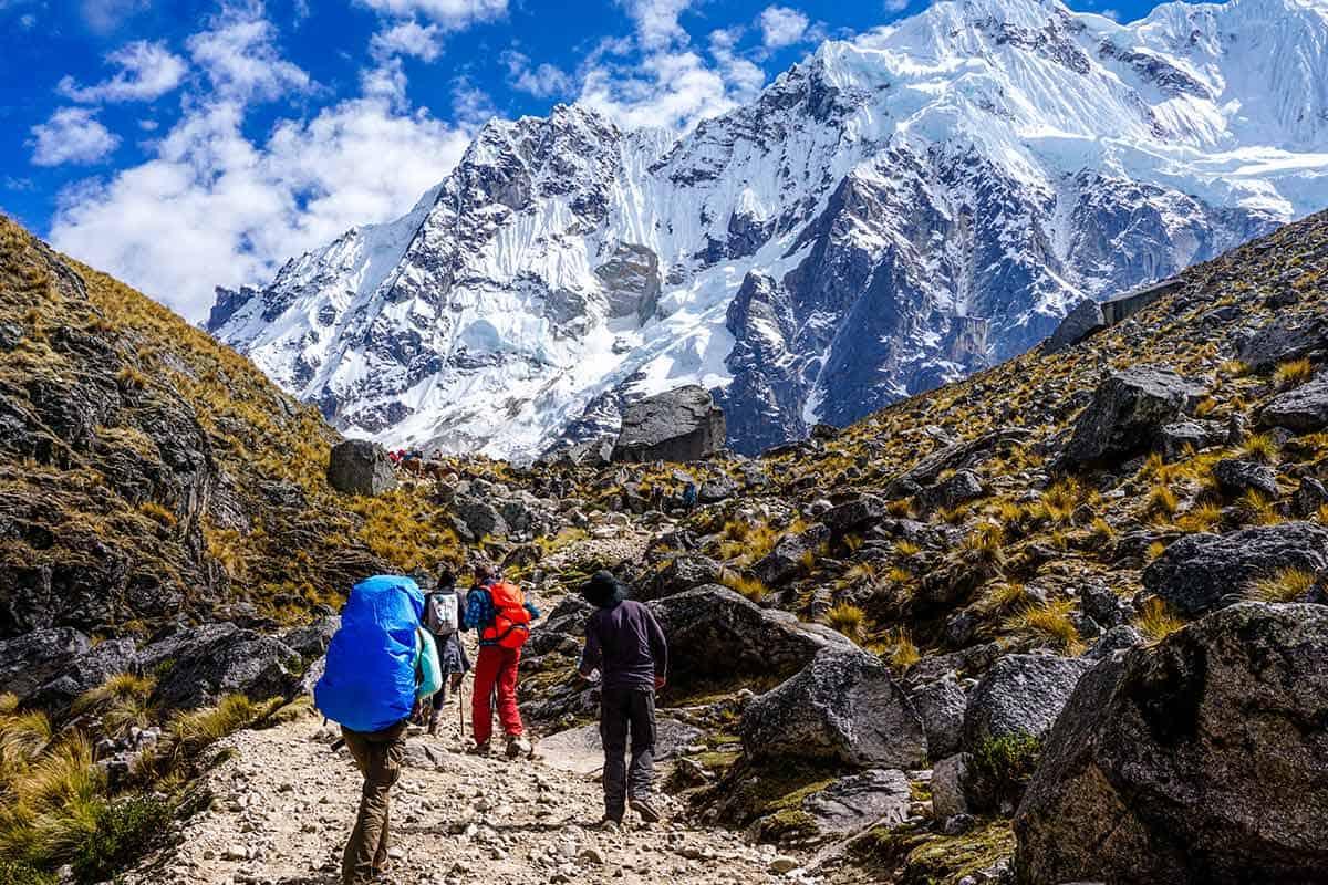 Trekkers wearing backpacks making a steep climb up a trail towards the snowcapped peak of Salkantay.