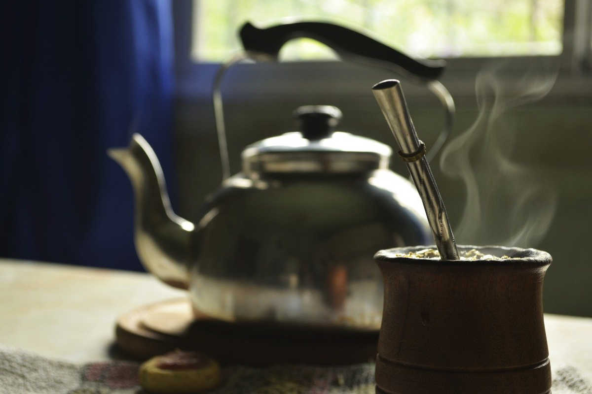 A cup of yerba mate, a popular beverage in Argentina with a stainless silver straw and kettle.