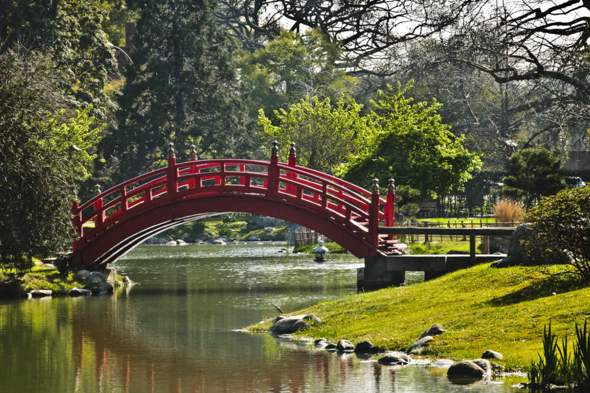 Red bridge over a lake and plants at the Japanese Garden in Parque 3 de Febrero in Buenos Aires.