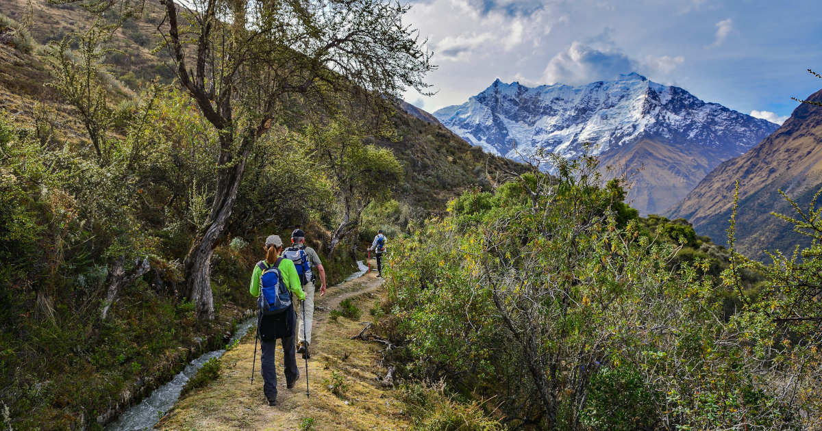 Group of 1 woman and 2 men hiking a green mountain trail toward a snowcapped peak in the Andes.