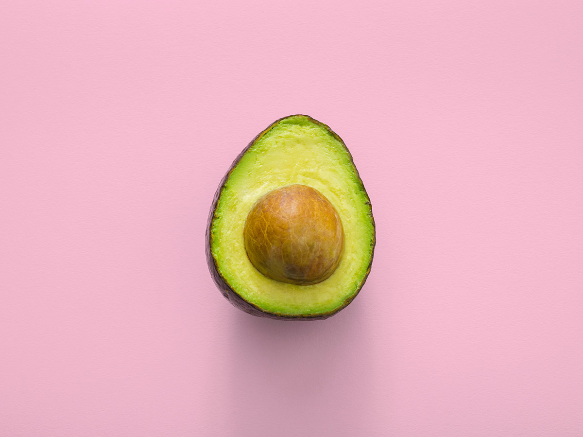 A sliced green avocado with the seed against a pink background.