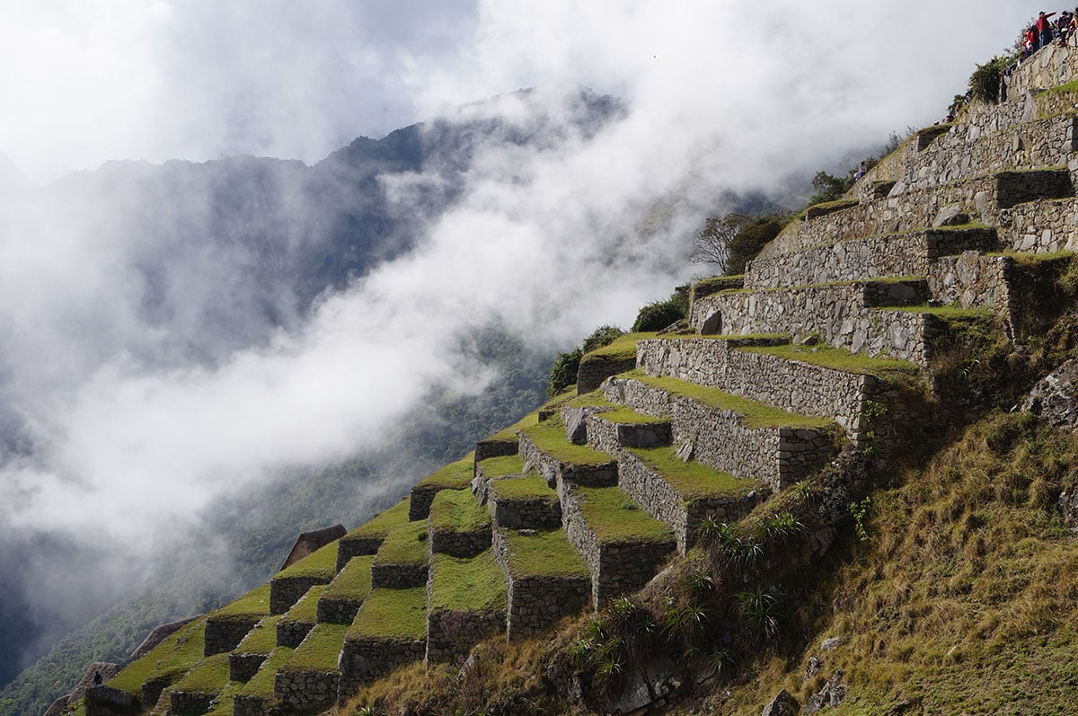 Clouds hover over the stone and grass terraces at Machu Picchu once used for agriculture