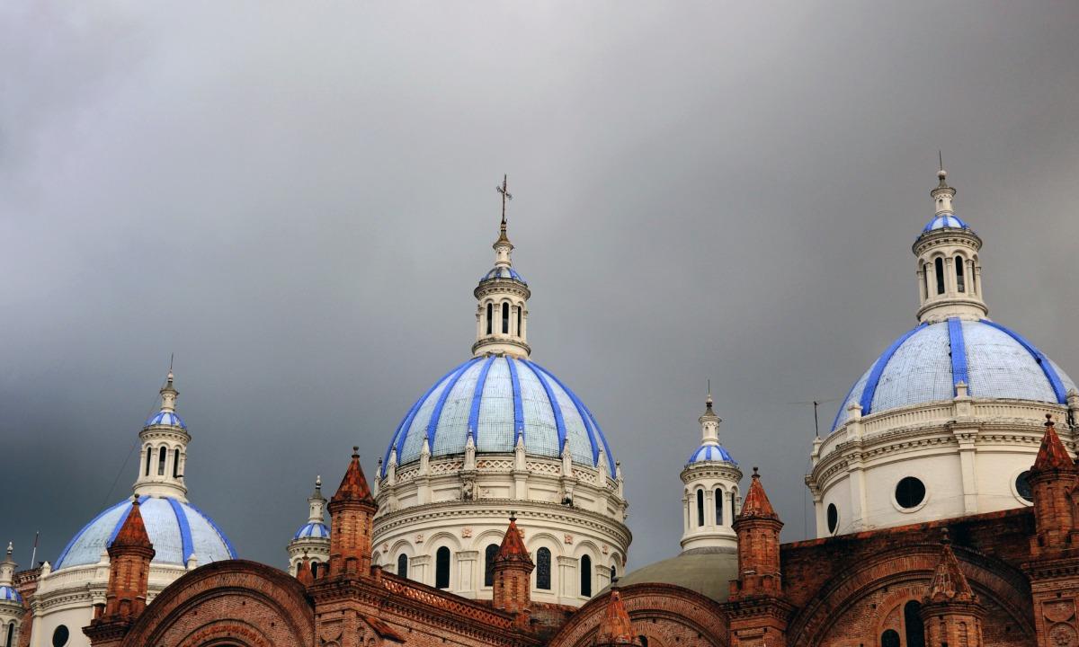 Three pale blue domes on a church in Cuenco, Ecuador against a dark grey sky.