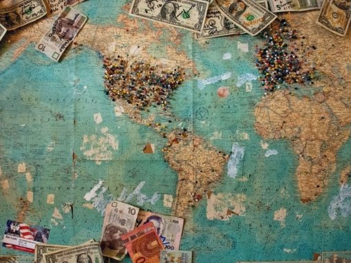 World map as seen from above with various local currencies on top.